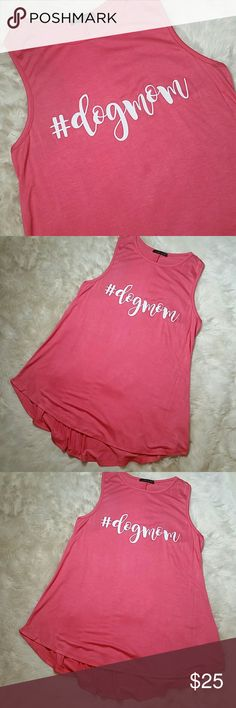 Dog Mom Flowy Racerback Tank Small Medium Large Dog Mom Flowy Racerback Tank Small Medium Large. Pinky salmon with white #dogmom graphic. Higher muscle tee collar and pulls into a racerback below the neckline. Flowy, relaxed and oversized. Split seam down the back. True to size for a loose fit through the torso and flowy hemline hits below the hips. Made in USA- soft, slinky and stretchy 96% rayon & 4% spandex. Available in sizes Small, Medium and Large. Tops Tank Tops