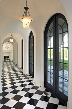 Hall by John Kraemer & Sons | black and white hallway | white walls with black doors | black and white tiled floor | dramatic home decor
