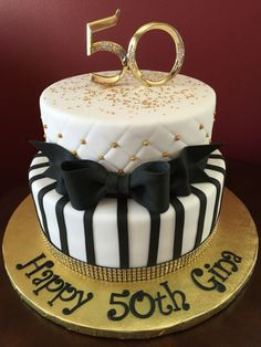 happy 50th gina, written in black on a white and gold cake, decorated with a black bow made from fondant, edible gold pearls and glitter, 50th birthday party ideas for mom, topper shaped like the number 50
