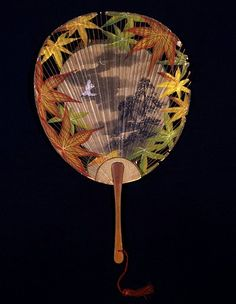 """Fan created in Japan in the year 1896 for a British stage production of the """"Mikado"""". Flat Japanese fan with bamboo handle and sticks and red silk tassel. The fan is printed with images of foliage and birds. V Museum"""