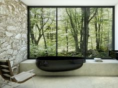 Bathroom Ideas: 12 Tubs with Amazing Views \\\ This tub from Beyond Bath by Claudia Danelon is made of a composite called Pietraluce in a glossy black, which is similar in appearance and weight to ceramic. It's almost as beautiful as the woodsy scene its set against.