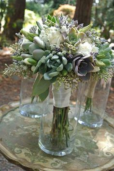 Minty succulents with white carnations, fresh lisianthus buds, fluffy babies breath and dried lavender. I wired the lisianthus buds individually and they held up beautifully for shipping and through the wedding. Soooo beautiful! Pricing: Bridal $185  Bridesmaid $65  Corsage $25  Boutonnière $15