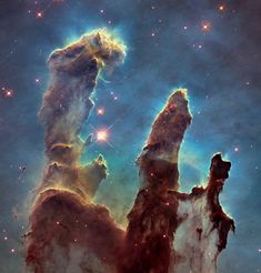 """One of the most iconic images ever produced by NASA is the """"Pillars of Creation"""" photograph taken by Hubble Space Telescope in 1995. The photo depicts tall columns (called elephant trunks) of interstellar dust and gas within the Eagle Nebula about 6,500 light years from Earth. For the first time in 20 years, NASA revisited the Pillars of Creation using a new camera installed on Hubble back in 2009 capable of much higher resolutions."""