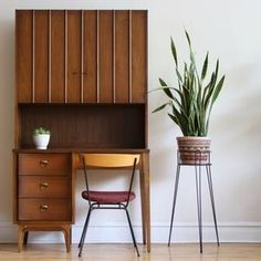 Mid-Century Modern walnut single pedestal desk with shelving hutch on top made by Johnson Carper. The four dovetailed drawers with brass hardware have a durable laminate desk surface.