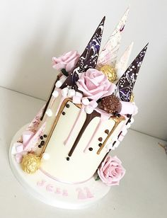 Pink, gold and dark chocolate drip cake finished with chocolate shards .
