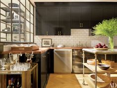 Berkus painted the existing kitchen cabinetry a high-gloss black by Farrow & Ball and added crown molding and brass pulls; the subway-tile backsplash, Electrolux dishwasher, and marble-top island are new.