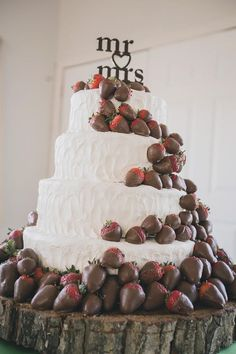 A white wedding cake covered with chocolate covered strawberries is an eye-catching and delicious wedding cake. #weddingideas