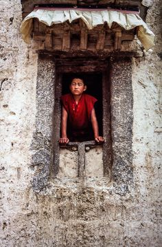 Young tibetan monk peeking out the window Shigatse, Tibet