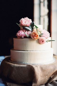 Simple 3 tier with peonies and roses on burlap stand. Best of wedding inspiration from around the globe.