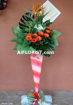 Colourful mixed of Gerberas, Tropical Heliconia & Cabbage flowers in this unique floral stand.