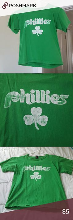 Phillies shamrock green t-shirt  (kids') Here is a Phillies shamrock t-shirt perfect for St Patrick's day or just to show off your regional and Irish pride. This is a kids XL, and I'm not sure as to whether it's specifically boys or girls. Has been worn a handful of times by myself (the kid's XL fit me perfectly as an adult size x-small). Was actually previously owned by my cousin. Some fading on the white print letters and shamrock. Shirts & Tops Tees - Short Sleeve