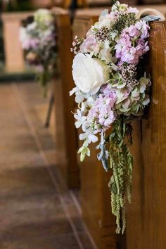 In a church wedding, large bouquets of cascading blooms add color and fragrance ~ https://www.insideweddings.com/weddings/east-coast-countryside-wedding-with-vintage-details/521/