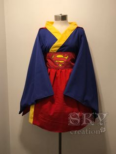 Supergirl Kimono Dress Includes: Kimono, Cape and Obi -Wide Collar -Kimono Sleeves -Detachable Cape -Lace Up Graphic with Decal Standard Sizes: XS-M Suitable for 32-37 Bust Bust: 38 Waist: 38 Hips: Open Shoulder to Shoulder: 16 Sleeve Length: 20 Kimono Length: 34 Obi: 85 L-XL Suitable