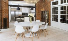 Industrial touch for dining area with exposed bricks on wall and tulip oval table