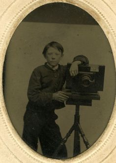 Young Boy Photographer Posed with His Camera on Tripod Before Simple Backdrop