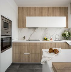 SANTOS kitchen | Cocina de Santos en vivienda reformada y decorada por Natalia Zubizarreta Interiorismo. El mobiliario en blanco y en acabado madera roble se combina con un azulejo entrepaño efecto mármol. Foto de Erlantz Biderbost. #cocinasSantos #blancoymadera