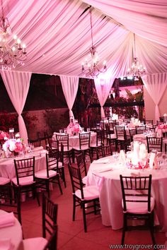 Tented reception with hanging chandeliers and pink uplights #Wedding #uplighting