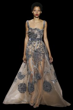 Long dress in black tulle, with a round collar neckline and long split sleeves, embellished with a beadwork «Love» made of silk threads and sequins.