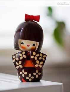 Kokeshi 'Kosode' véritable Kokeshi Japonaise entièrement réalisée à la main au Japon. Cette Kokeshi de 16 centimètres représente une jeune fille portant un kimono de couleur marron à manche courte. Bois : Cornouiller