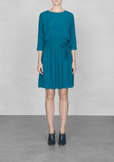 A relaxed, lightweight dress with three-quarter sleeves and a fold-over front that buttons on the side.
