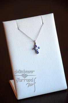 This 18 karat white gold necklace has one diamond and 5 blue sapphires. #mitchenerfarrand