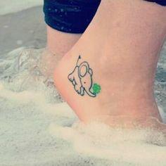 Little elephant tattoo holding a four-leaf clover on Anika.