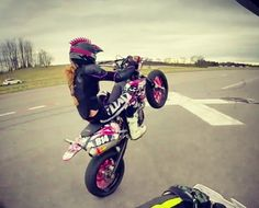 Pink mohawk girl on motorcycle doing a wheelie