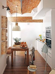 Barcelona apartment- rustic wood cut out & exposed brick in the galley kitchen.