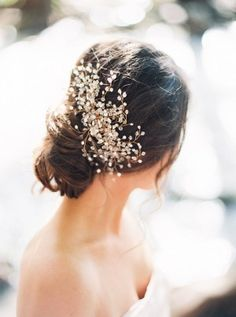 Low bun with floral inspired hair piece | Photo: Loft Photography
