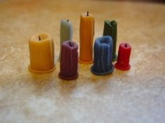 Used cut crayon, on button base melted top with a flame, inserted blackened wire for wick