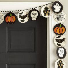 Halloween Disc Garland - Featuring a spooky cast of characters—ghost, skeleton, bat, haunted house and pumpkin—our Halloween garland sets the mood for Halloween. Embroidered and appliquéd on wool felt, the whimsical discs are suspended from a black-and-white twisted cord.