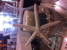 Lake house or beach theme idea. Sand, shells, candle....putting starfish inside instead of gluing to outside.