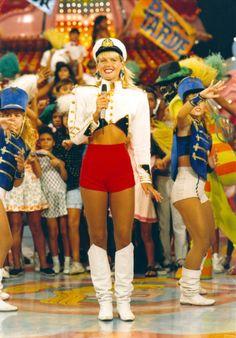 Xuxa de roupa de marinheira no cenário do Xou da Xuxa, com paquitas e crianças ao fundo