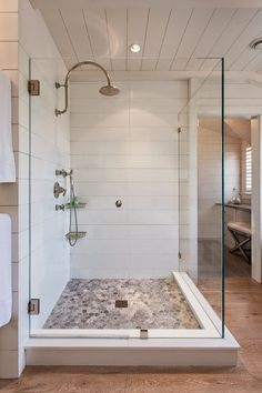 Love the clean cottage look of this frameless glass enclosure with beach inspired pebble rock shower floor
