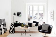 This mnochrome minimalist Scandinavian living room keeps things interesting with a mix up patterns and a splash of dark green.
