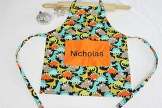 Personalized Dinosaurs on Black Child Apron with orange pocket - made to order Black Kids, Apron, Trending Outfits, Unique Jewelry, Handmade Gifts, Etsy, Clothes, Vintage, Fashion