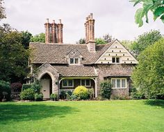 This English cottage has so many curb appeal elements - chimney pots, dove cotes, dormer windows, arched entry.