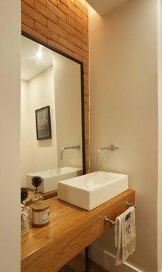 Em uma das paredes do lavabo, o pelo contraste entre os tijolos e o espelho. Obra da Escala Arquitetura Divulgação