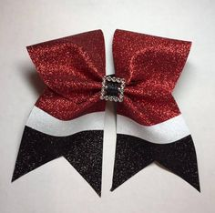 The base of the bow is 3 black, grosgrain ribbon and the overlay is red, black and white, glitter material. The bow measures approximately 7 wide and 6.5 from top to bottom. It is attached to a black pony o and all ribbon ends have been heat sealed to prevent fraying.  As with all
