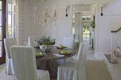 Cottage dining room boasts full wall board and batten lit by Ruhlmann Single Sconces in Bronze alongside a round dining lined with natural linen slipper dining chairs illuminated by a cream wood chandelier atop diamond jute rug layered over white oak floors placed in front of stained doors dressed in horizontal stripe curtains.