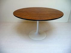 Please contact us for a shipping quote.  This Saarinen-style round tulip table is from Burke. It has a great solid wood top with black edges. The top is in good vintage condition with slight signs of wear and the white tulip only has minor chips. Overall its in very good vintage condition.  The dining table is 48Diam x 29H.
