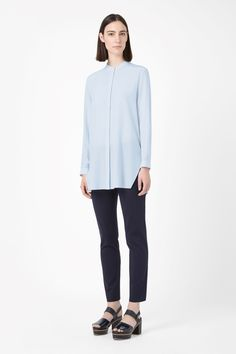 Made from pure silk with a smooth, matte finish, this long collarless shirt has hidden front buttons for a minimal finish. A straight-cut style, it has button cuffs, side splits and neat stitched edges.