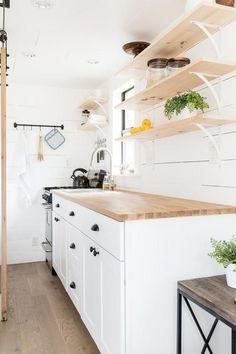 The kitchen has a propane gas range, open shelving, and butcher block countertop.