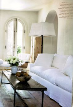 Pam Pierce - love those windows/doors! And the bright white couch + rustic wood coffee table.