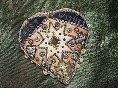 """This heart-shaped soldier's pincushion has a pinbeaded """"Best Wishes"""" message at its center. (Courtesy of The Way We Lived Then Museum, Eastbourne, England) Embroidery Tools, Vintage Sewing Notions, Textiles, Wool Applique, Sewing Accessories, Vintage Valentines, Diy Arts And Crafts, Pin Cushions, Heart Shapes"""