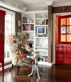 Chiang Mai covered chair, white bookcases, red door, dark walls.