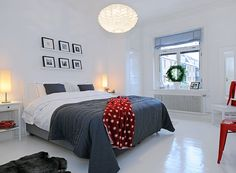 Minimalist white and grey bedroom with bold red accents