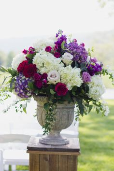 Altar flowers in a stone urn in soft whites mixed with deep purples, pink and lavender