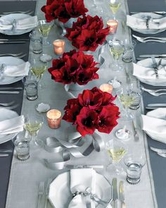 Bouquets of bold-red amaryllis tied with stiff silver ribbon and displayed down the center of a table look stunning against the hushed gray, white, and silver setting.