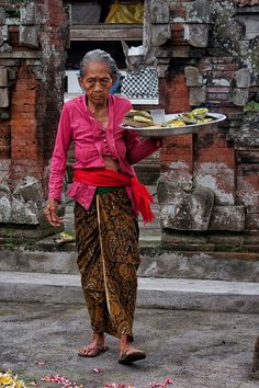 An old Balinese woman hauling bundles of stalks in Bali, Indonesia  hard work until the very